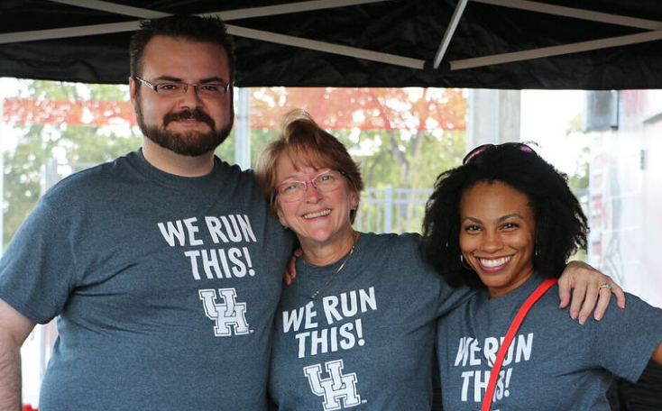 Adults Wearing We Run This UH Shirts