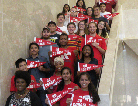 University of Houston Students Standing Along Marble Stairway with Go Coogs! Flags